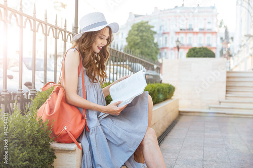 Plakat Cheerful young woman sitting and reading book in the city