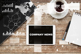 Tablet on desktop with company news text. - 142361475