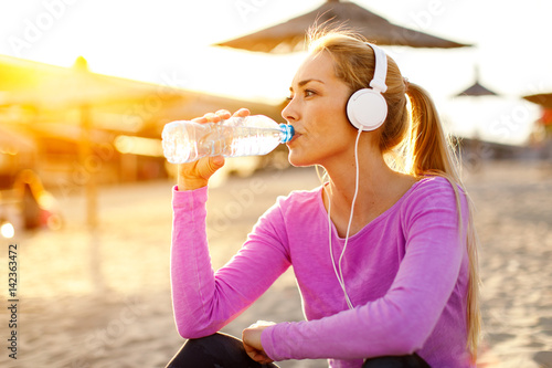 Foto Murales Beautiful woman drinking water and listen to music after running on the beach at sunset