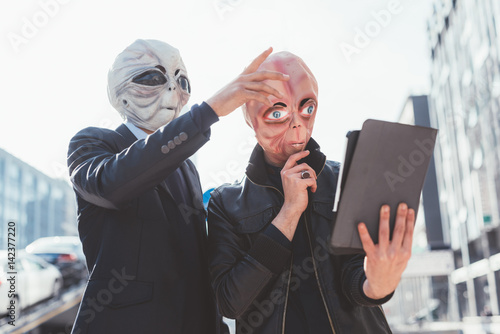 Two man wearing alien masks using tablet hand hold outdoor in city back light - Poster