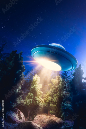 Poster High contrast image of UFO flying over a forest with light beam at night