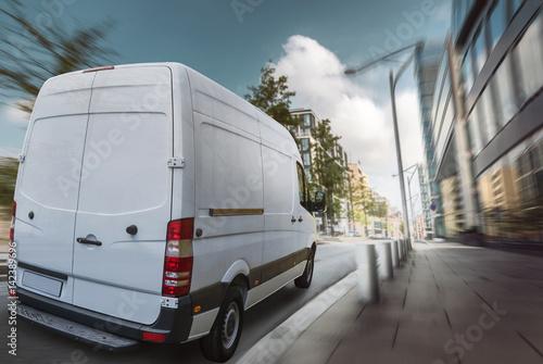 Fototapeta Lieferwagen fährt am Tag durch eine Stadt
