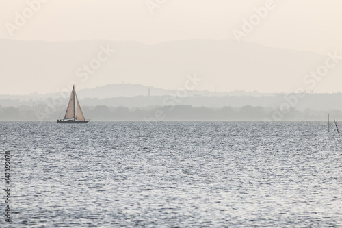 A small sailboat on a lake, with distant hills in the background, and very soft colors, mostly white and light blue - 142399078