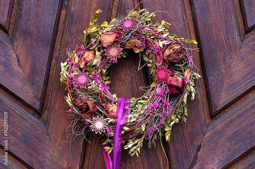 Wreath on a door.Rustic wooden door with decorative wreath. Poster