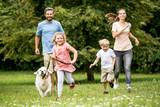 Kinder und Eltern laufen mit dem Hund