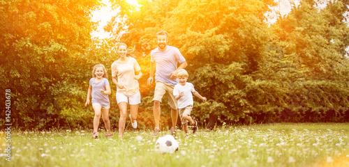 Familie mit Ball spielt Fußball im Sommer