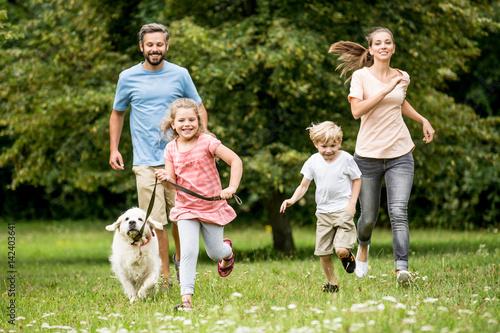Poster Kinder und Eltern laufen mit dem Hund