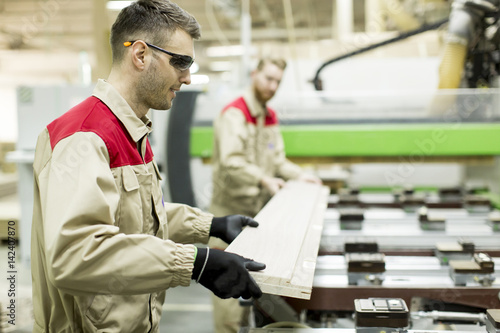 Young men working in furniture factory - 142407870