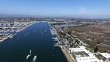 Panoramic fly over Long Beach marina and harbor with speed boats, yachts and sky jets