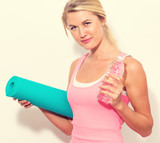 Woman holding yoga mat and water bottle