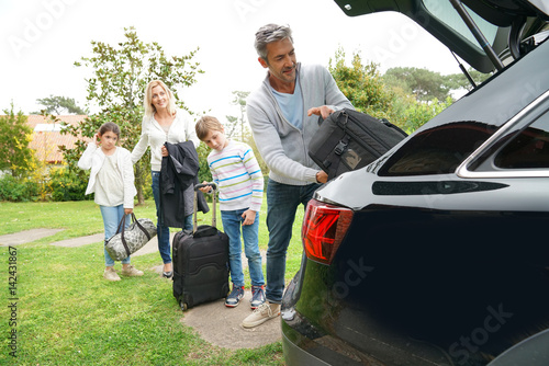 Family of four loading car trunk to leave for vacation Poster