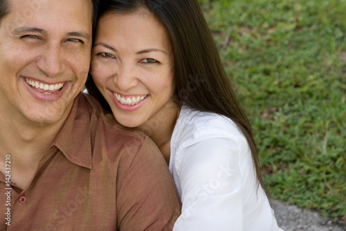 Poster Portrait of an Asian couple laughing and hugging.