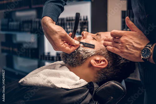 Barber shaving bearded male with a sharp razor.