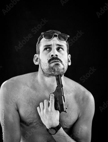 Keuken foto achterwand Vlinders in Grunge Shirtless athletic guy holding handgun under his chin on black background. Vertical portrait