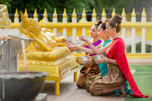 Poster Asiatic woman are bathing Buddha statue happily in thailand.