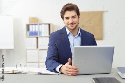 fototapeta na ścianę seriöser berater sitzt am schreibtisch und arbeitet am notebook