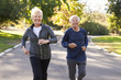 Senior Couple Jogging Through Park