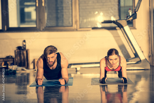 Young sporty man and woman doing plank exercise on mats in gym
