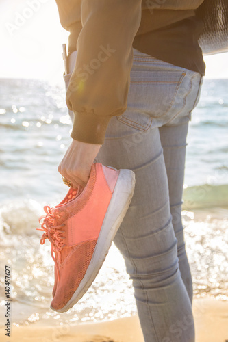 Poster Junge Frau in blauen Jeans hält Sneakers im Gegenlicht