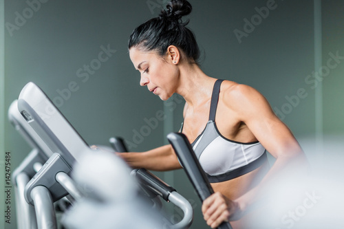 Wall mural Side view  portrait of sweaty fit woman exercising using elliptical machine  during intense workout in modern gym