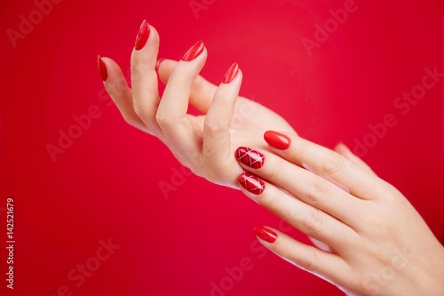 Papiers peints Manicure Beautiful manicured woman's hands on red background.