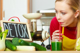 Woman holding vegetable juice and detox sign