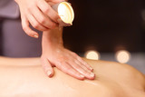 woman doing back massage with hot oil at spa