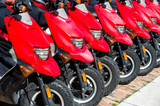 red scooters or motorcycles for sale or hire in row