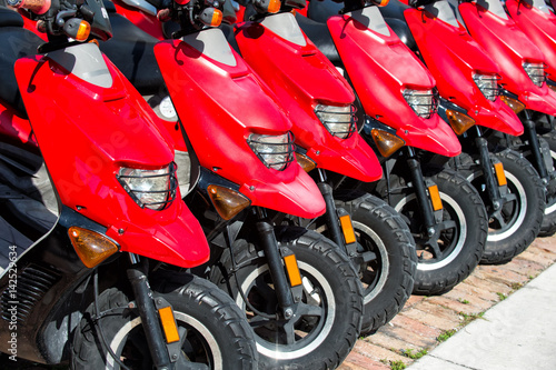 Foto op Aluminium Scooter red scooters or motorcycles for sale or hire in row