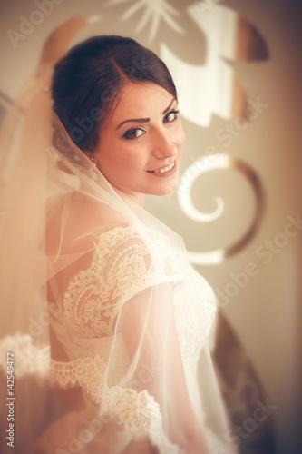 Plakat Beautiful bride in white wedding dress standing near the window