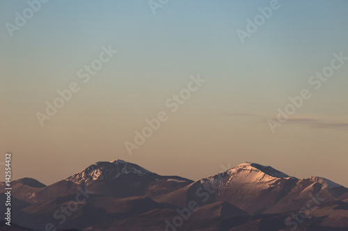 A minimalist view of some mountains top with snow, under a big, almost empty sky, with golden hour warm colors - 142554432