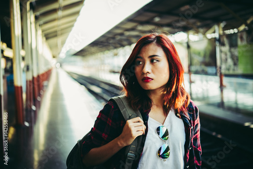 Young hipster woman waiting on the station platform with backpack Poster