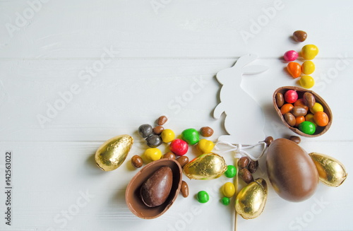 White Easter bunny with chocolate eggs and candies on white wooden background