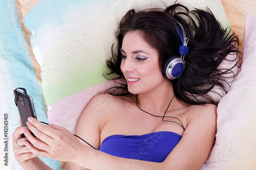 Pretty girl listening to music relaxing in her coloured bed with her smartphone Poster