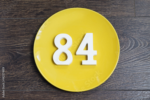 Poster The number eighty-four on the yellow plate.