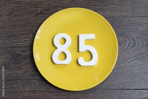 Poster The number eighty-five on the yellow plate.