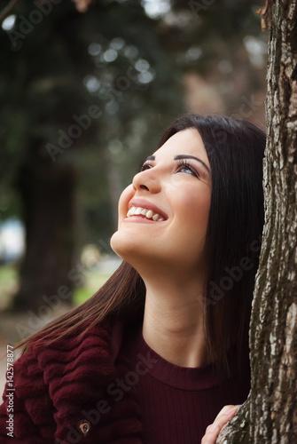 Giovane adulta sorridente dietro un albero nel parco nella natura