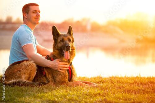 Poster Relaxed man and dog enjoying summer sunset or sunrise