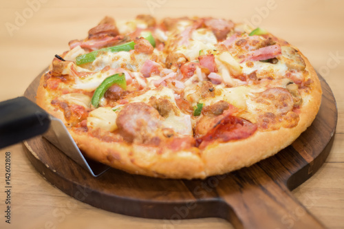 Close up of supreme pizza with ham pepperoni and cheese on wooden pan Poster