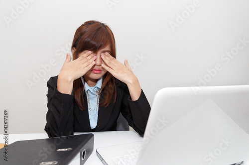 Poster Businesswoman with eyes pain at office desk - business concept.