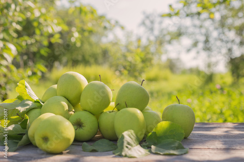 Poster green apples on wooden background outdoor