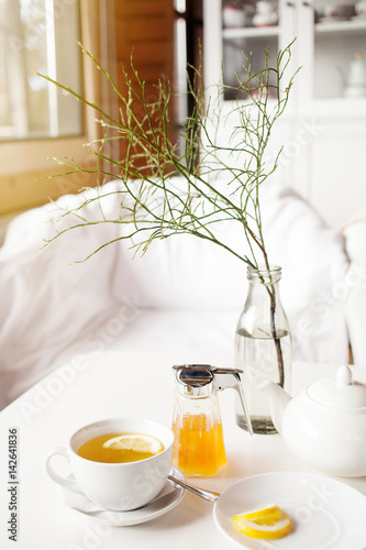 Cup of hot green tea with lemon on white table, fresh lemon and honey - closeup shot Poster