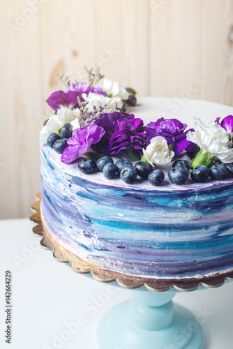 Colorful wedding cake with lovely purple flowers and blueberries