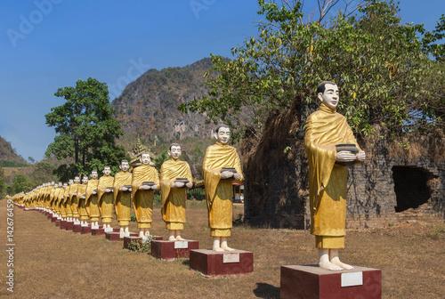 Poster many buddha statues standing in row at Tai Ta Ya monastery temple in payathonzu