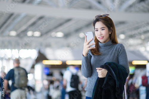 In de dag Tunnel Charming beautiful business woman smile in casual style using smartphone and hold luggage bag for travel with blur the airport terminal.