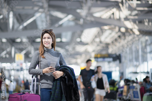 In de dag Tunnel Charming beautiful business woman smile in casual style using smartphone with blur the airport terminal.