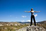 femme au sommet des montagnes en été les bras en l'air