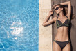 Young slim beautiful woman in bikini sunbathing near swimming pool.
