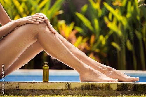 Young slim beautiful woman in bikini applying oil for sun protection Poster