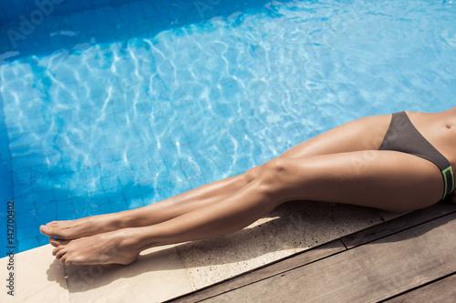 Beautiful woman legs sunbathing near swimming pool.